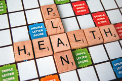 Health Plan. The words health and plan on a scrabble board Royalty Free Stock Photo