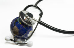 Health of the planet Earth. Small Earth like  globe under the capsule of a medical stethoscope , conceptual image about environmental health of the planet Stock Photo