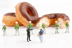 Health Police. Tiny police in riot gear preventing an overweight man from reaching donuts a public health obesity concept selective focus on foreground figures Royalty Free Stock Photography