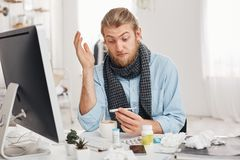 Health problems concept. Astonished young bearded office worker has a bad cold, flu, looks at thermometer with bugged Stock Photography