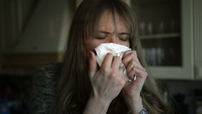 Health problems for young woman sneezing in the kitchen.