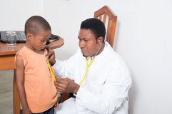 Health professional examining a child. The health professional is about to listen to the heartbeat of that child Stock Photos