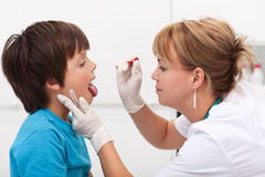 Health professional taking saliva sample from boy Royalty Free Stock Image