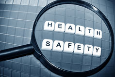 Health and safety. Focus on health and safety concept with magnifying glass and key words Royalty Free Stock Photography