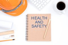 Health and safety concept. Top viwe of modern workplace with safety helmet, office supplies, a cup of coffee and keyboard on whit. E background royalty free stock photos