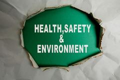 HEALTH, SAFETY AND ENVIRONMENT CONCEPT text at plain torn paper. stock photo