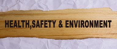 HEALTH, SAFETY AND ENVIRONMENT CONCEPT text at plain torn paper. stock images