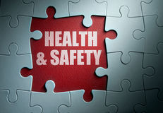 Health and safety. Missing pieces from a jigsaw puzzle revealing health and safety Stock Images
