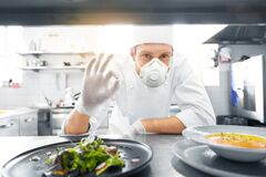 Male chef in mask with food at restaurant kitchen