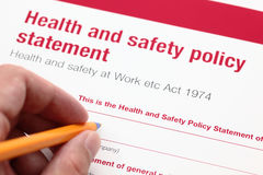 Health and safety policy statement. Health and safety policy statement and hand with ballpoint pen Royalty Free Stock Photo