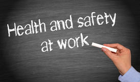 Health and safety at work. Female hand writing text on blackboard Royalty Free Stock Photos