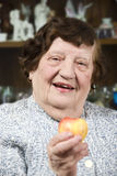 Health senior woman with fruit. Health senior woman sitting on chair in her living room  offering an apple and smiling,check also  Grandmother Stock Images