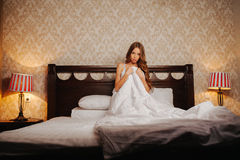 Naked woman covered by the blanket on the bed stock image