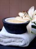 Health spa. Organic vanilla candle with oriental lilly and white towel to convey the concept of luxury and relaxing spa resort and health club treatments Royalty Free Stock Photos