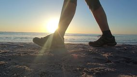 Health, sport and wellness. Slow motion close to the ground of young woman walking at dawn with sneakers along the shore and the s. Un in backlight slips between stock video