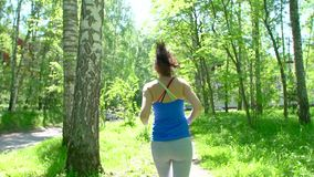 Health sport young woman run and look wear smart watch device. Young sporty woman preparing to jog, starts a workout. Tracking on a smart watch. sun glares stock footage