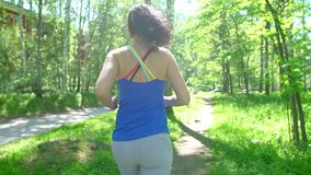 Health sport young woman run and look wear smart watch device. Young sporty woman preparing to jog, starts a workout. Tracking on a smart watch. sun glares stock video