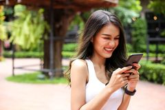 Health sport young woman typing text message on smart phone and. Talking to Someone on her Mobile Phone royalty free stock photography