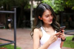 Health sport young woman typing text message on smart phone and. Talking to Someone on her Mobile Phone stock photo