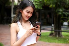 Health sport young woman typing text message on smart phone and. Talking to Someone on her Mobile Phone royalty free stock image