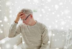 Senior man suffering from headache at home. Health, stress and people concept - senior man suffering from headache at home over snow Stock Photo