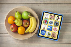 Health App Apps Diet Fruit Technology. A bowl of fruit with a computer tablet on a wood background. Tablet has concepts about health and nutrition ways of living royalty free stock images