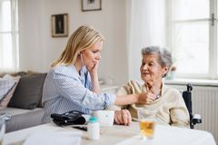 A health visitor examining a senior woman with a stethoscope at home. A young health visitor examining a senior women with a stethoscope at home stock image