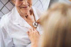 A health visitor examining a sick senior woman lying in bed at home with stethoscope. A midsection of young health visitor examining a sick senior women lying royalty free stock photo