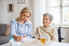 A health visitor explaining a senior woman in wheelchair how to take pills. A young health visitor explaining a senior women in wheelchair how to take medicine stock photography