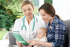 Health Visitor Giving Mother Leaflet With Advice On Baby. Health Visitor Gives Mother Leaflet With Advice On Baby royalty free stock photography