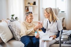 A health visitor giving a senior woman a glass of water to take pills. A health visitor giving a senior women a glass of water, explaining her how to take pills royalty free stock photos