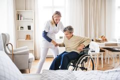 A health visitor helping a senior woman to stand up from a wheelchair. A young health visitor helping a senior women to stand up from a wheelchair at home royalty free stock images