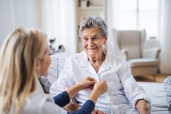 A health visitor helping a sick senior woman sitting on bed at home. A young health visitor helping a happy sick senior women sitting on bed at home stock photos