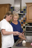 Health visitor on a home visit with elderly lady Stock Photography
