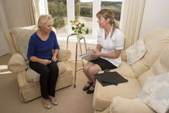 Health visitor on a home visit with elderly lady. Nurse on a home visit talking with an elderly female patient Royalty Free Stock Photography