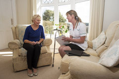Health visitor on a home visit with elderly lady. Nurse on a home visit talking with an elderly female patient Stock Image