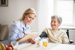 A health visitor measuring a blood pressure of a senior woman at home. A young health visitor measuring a blood pressure of a senior women in wheelchair at home royalty free stock image