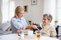 A health visitor measuring a blood pressure of a senior woman at home. A young health visitor measuring a blood pressure of a senior women in wheelchair at home stock photography