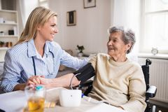 A health visitor measuring a blood pressure of a senior woman in wheelchair at home. A young health visitor measuring a blood pressure of a senior women in royalty free stock photos