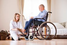 Nurse and senior man in wheelchair during home visit. Health visitor or a nurse and a senior men in a wheelchair during home visit. A nurse helping a senior men Stock Image
