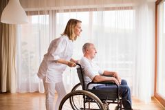 Nurse and senior man in wheelchair during home visit. Health visitor or a nurse and a senior men in a wheelchair during home visit. Man and women looking out of Royalty Free Stock Images