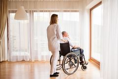 Nurse and senior man in wheelchair during home visit. Health visitor or a nurse and a senior men in a wheelchair during home visit. Man and women looking out of Stock Photo
