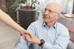 Health visitor and a senior man during home visit. Happy patient is holding caregiver for a hand while spending time together royalty free stock image
