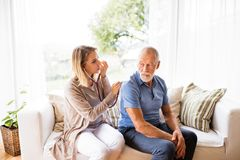 Health visitor and a senior man during home visit. Health visitor and a senior men during home visit. A female nurse or a doctor examining a man Stock Image