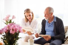 Health visitor and a senior man during home visit. Health visitor and a senior men during home visit. A female nurse or a doctor discussing test results Royalty Free Stock Image