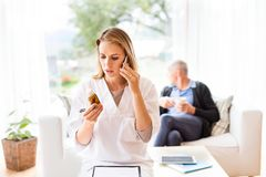Health visitor and senior man during home visit. Health visitor with smartphone and a senior men during home visit. A female nurse or a doctor making a phone Royalty Free Stock Photo