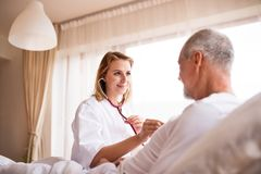 Health visitor and a senior man during home visit. Health visitor and a senior men during home visit. A female nurse or a doctor examining a man Royalty Free Stock Photo