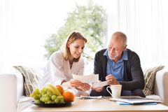 Health visitor and a senior man with tablet during home visit. Health visitor and a senior men during home visit. A female nurse or a doctor discussing test Royalty Free Stock Photos