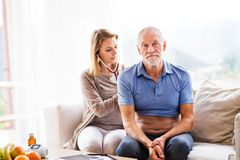 Health visitor and a senior man during home visit. Health visitor and a senior men during home visit. A female nurse or a doctor examining a man Royalty Free Stock Images