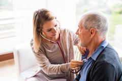 Health visitor and a senior man during home visit. Health visitor and a senior men during home visit. A female nurse or a doctor examining a man Royalty Free Stock Photography